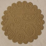 Chip board coasters die cut and embossed with same embossing pattern on glass candle holder.