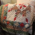 Old quilts and pillows at the ready for a nap, hosted by an old tobacco gathering basket.