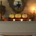 White pumpkins, a large wood finial, candles and orange velvet ribbon woven through a moss lined wire basket