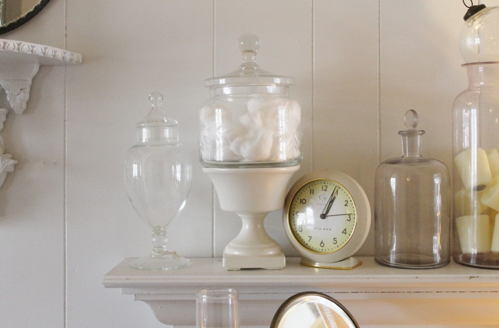 A variety of vintage jars collected from all over next to a vintage reproduction clock.