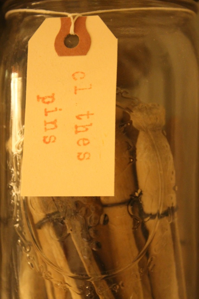 Vintage Mason Jars filled with old wood and wire clothes pins with a sweet home made label