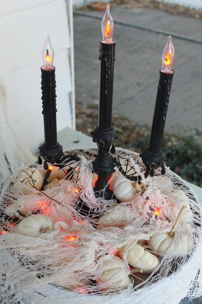 Some small white pumpkins act as filler to hide power cords and white gauze mutes the bright orange holiday string lights.