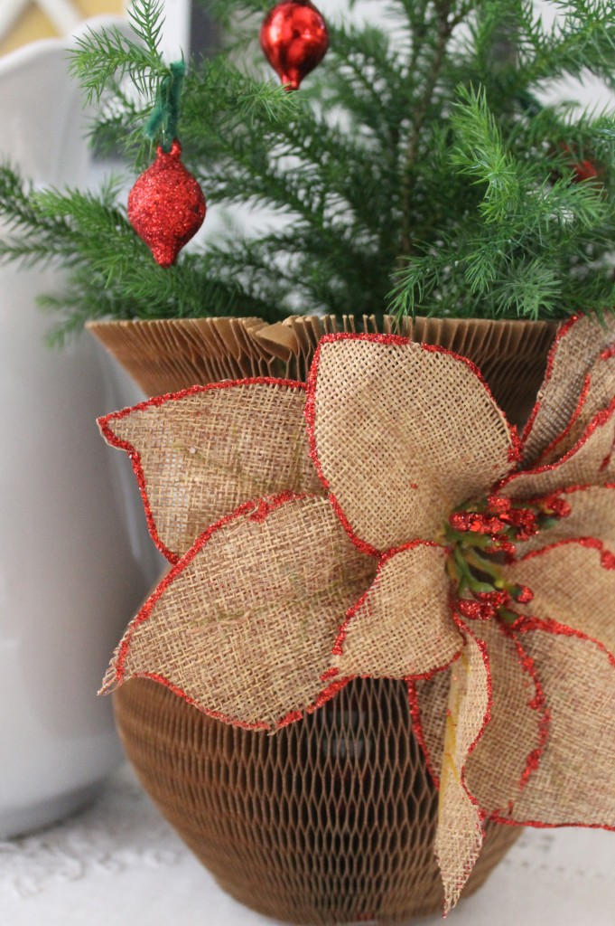 A vintage paper vase cover for a holiday touch with a market item burlap flower embellishment from Michael's ($2.50)