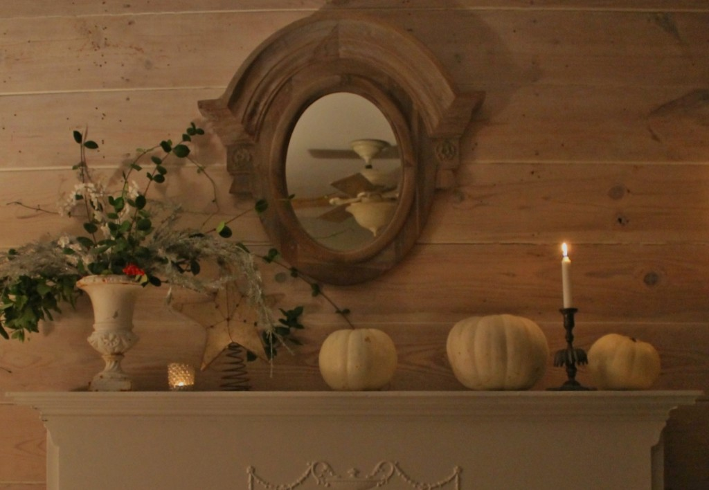 The white pumpkins signal fall and winter along with a distressed star shaped mirror and winter arrangment