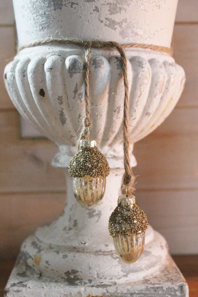 Against the worn surface of the urn, small acorn mercury glass ornaments from Targets ($4 for three).  Simple rustic twine will do for hanging.