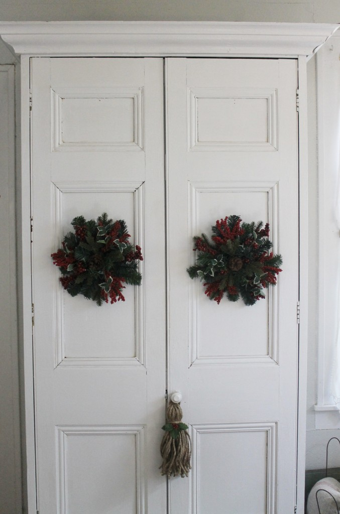 Old houses have many armoires for storage.  Simple white adorned with  wreaths and a hand-made twine tassel with holiday embellishment.