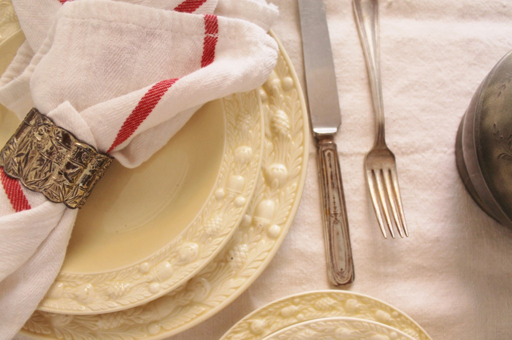 Lovely cream antique china and mismatched silverware and napkin rings.  The market item in this photo is an inexpensive kitchen towel used as a napkin from IKEA for .79 cents.