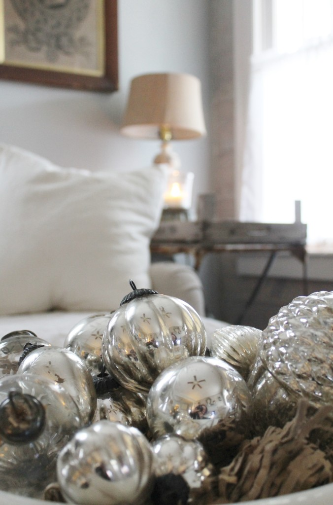 Mercury glass globes in an old ironstone bowl with linen slipcovers in the background.