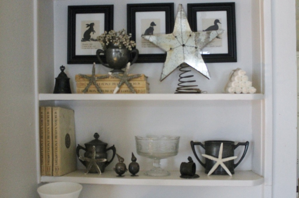 a variety of neutral toned items arranged on a shelf.