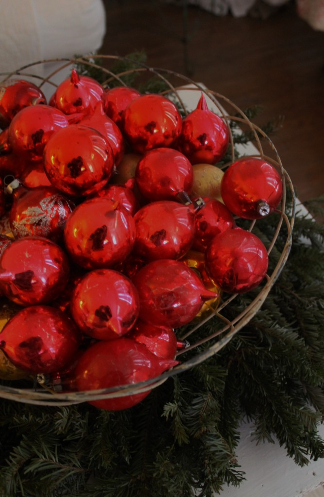 Vintage, hand blown ornaments in a wire basket, setting softly on  a wreath on my coffee table.