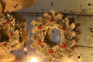 Glittery little wreath ornaments on an old, mottled mirror.