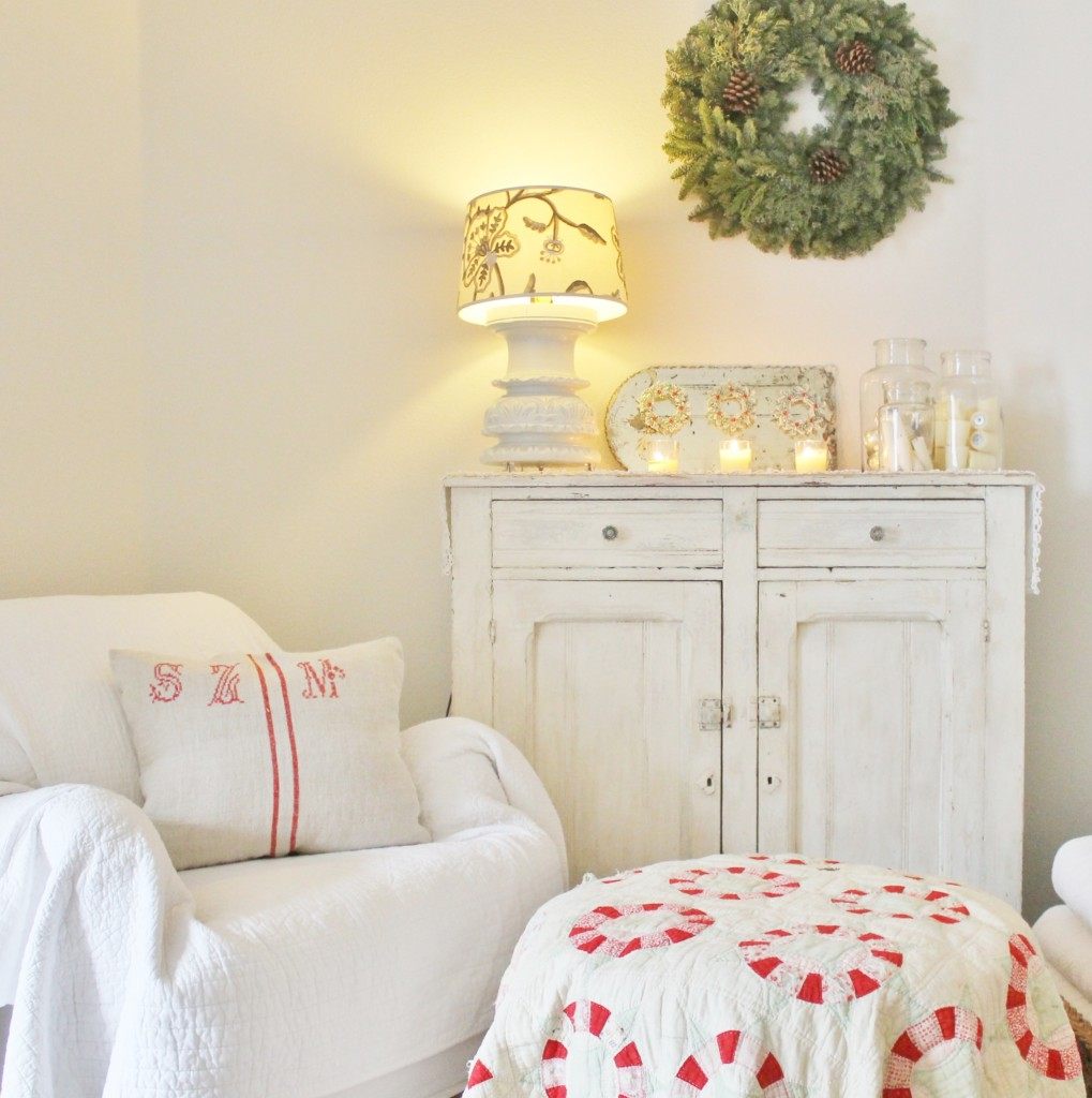 A little nook in my apartment with a simple wreath, some candles and a lovely quilt with lovely festive colors for some contrast.