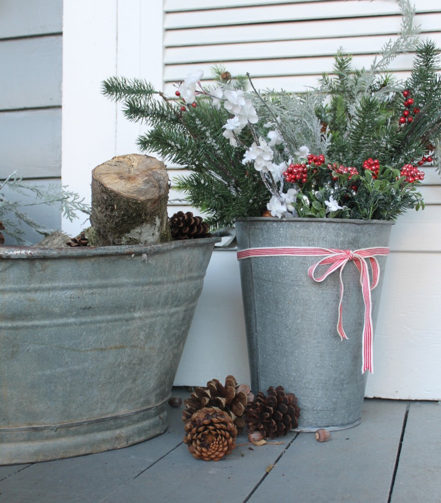 A sap bucket, artificial greens missed with seasonal greens and an old galvanized tub filled with logs.