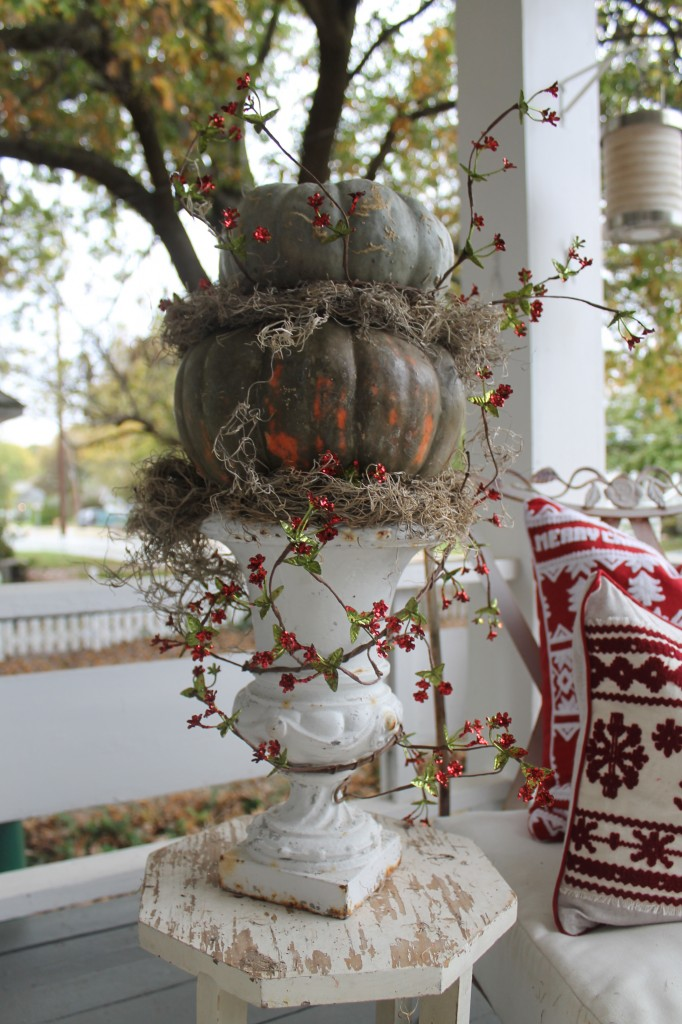 Fall pumpkins, stacked and tucked with moss, followed by a Christmas garland presented in an old cast iron urn. It's one way to transition from fall to Christmas, using what you already have.