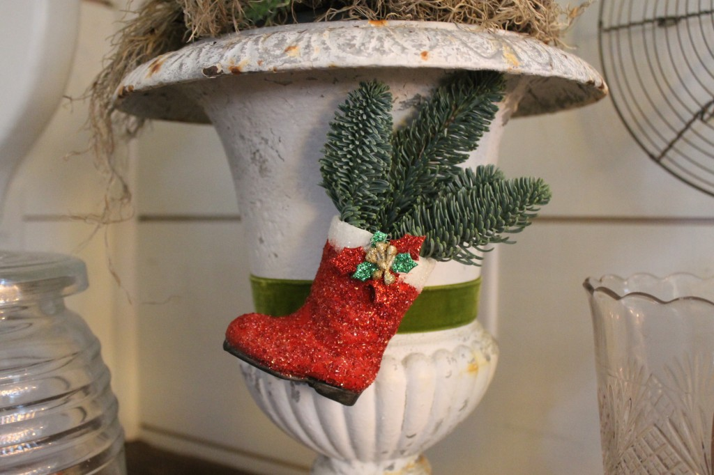 A papier mache Santa boot that I painted then adorned with German Glitter Glass and a holiday embellishment, topped off with a fresh sprig of greens.