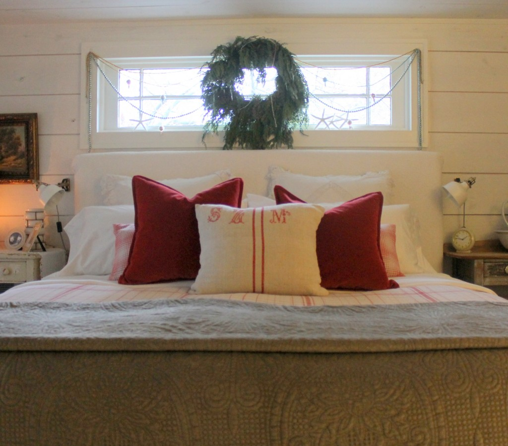A simple fresh green wreath flanked by antique mercury glass beaded garland.  The bed is simply dressed with vintage linens and ruby red washed velvet pillows and a quilted velvet blanket at the end of the bed in a subdued neutral color.  It all makes for a cozy place to be.
