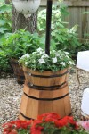 Two cedar planters, one smaller and one larger were used.  Purchased from Lowe's, a hole was drilled in both of them to allow them to slide down the center pole.  The larger was turned upside down, the smaller was filled with some plastic at the bottom, potting soil and flowers.  A simple pressure fit (with the help of a rubber mallet) was all that was needed to create one unit.
