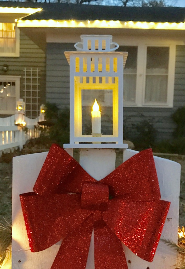 An Ikea lantern with a battery operated candle for each fence post.